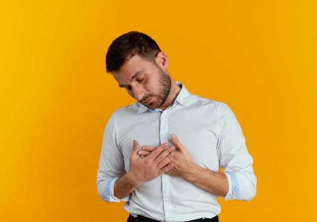 Schläfriger gutaussehender mann legt hände auf brust isoliert auf orange wand