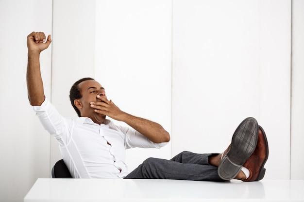 Schläfriger junger erfolgreicher geschäftsmann, der gähnt und am arbeitsplatz sitzt