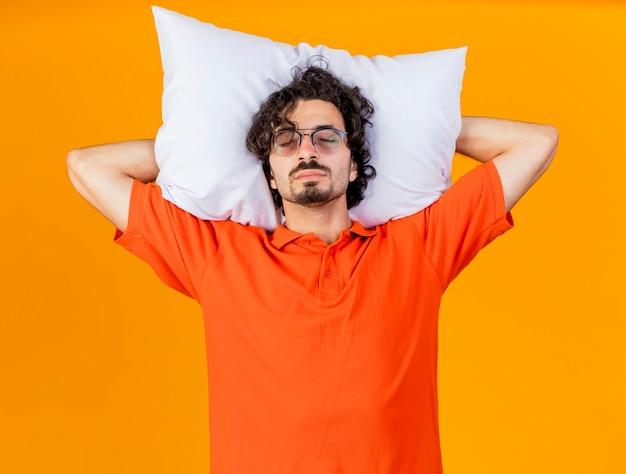 Schläfriger junger kaukasischer kranker mann, der eine brille trägt, die kissen unter kopf hält, so tut, als würde er mit geschlossenen augen schlafen, die auf orange wand isoliert sind