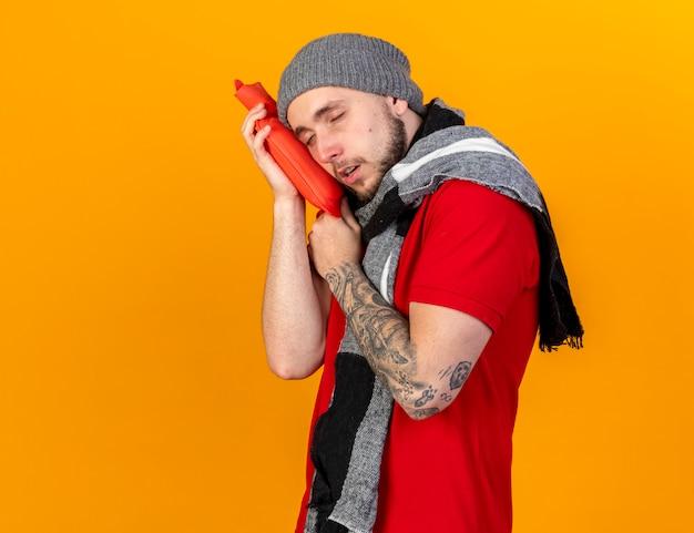 Schläfriger junger kaukasischer kranker mann, der wintermütze und schal trägt, setzt kopf auf wärmflasche lokalisiert auf orange wand mit kopienraum