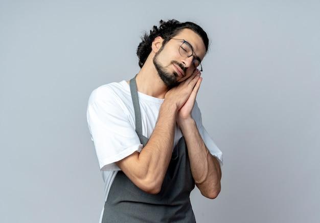 Schläfriger junger kaukasischer männlicher friseur, der brille und gewelltes haarband in der uniform tut, die schlafgeste mit geschlossenen augen tut, lokalisiert auf weißem hintergrund mit kopienraum