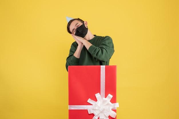 Schläfriger junger mann der vorderansicht mit der partykappe, die hinter der großen geschenkbox auf gelbem hintergrund steht