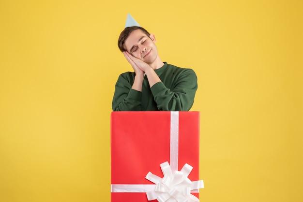 Schläfriger junger mann der vorderansicht mit der partykappe, die hinter großer geschenkbox auf gelb steht