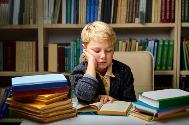 Schläfriger kleiner junge, müde vom lernen, hausaufgaben zu lesen, zu studieren, sich auf prüfungstests vorzubereiten, literaturrecherche, kindererziehungskonzept