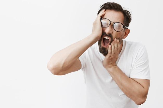 Schläfriger lustiger bärtiger reifer mann mit der aufstellenden brille