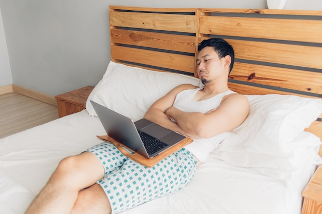 Schläfriger mann arbeitet mit seinem laptop auf seinem gemütlichen bett. konzept des langweiligen freiberuflerlebensstils.