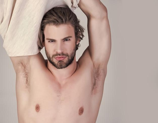 Schläfriger mann ausziehen. mann mit zerzausten haaren in unterwäsche. schlaflosigkeit, energie, single mit ungekämmten haaren. morgen aufwachen, alltag