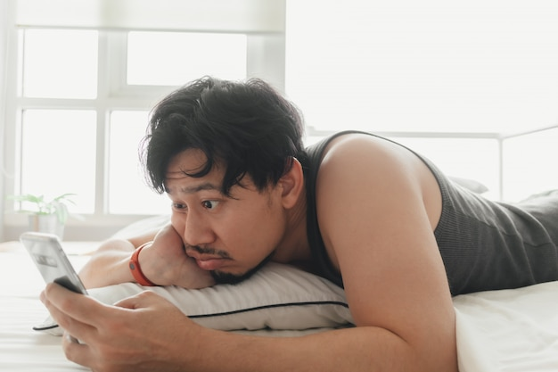 Schläfriger mann benutzt smartphone, während er auf dem bett liegt.