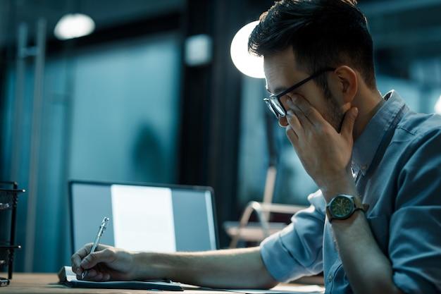 Schläfriger mann, der spät im büro arbeitet