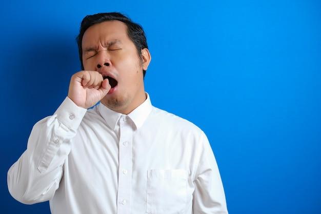 Schläfriger müder asiatischer geschäftsmann, der gähnt, im stehen schläft, halbes körperporträt über blauem hintergrund
