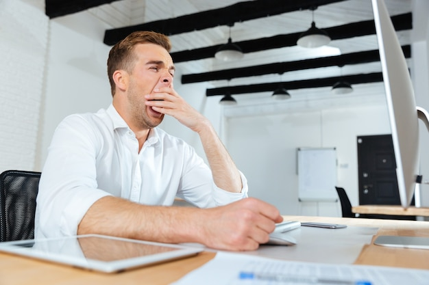 Schläfriger müder junger geschäftsmann, der im büro arbeitet und gähnt