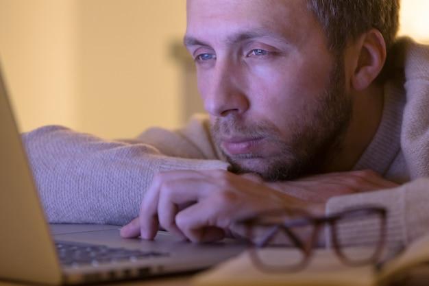 Schläfriger müder mann designer, der am laptop arbeitet / tippt