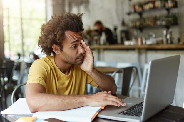 Schläfriger student mit buschigem haar und dunkler haut, der seine augen mit der hand reibt, während er in den bildschirm des laptops schaut, der müde schlafen will, um sich auf abschlussprüfungen vorzubereiten.