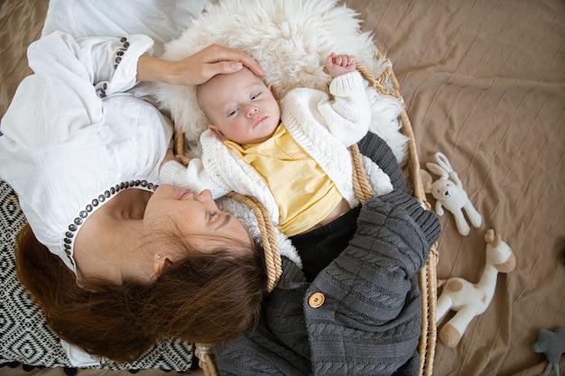 Schläfriges baby in einer weidenwiege in der wärme nahe einer glücklichen fürsorglichen mutter auf dem hintergrund einer decke mit spielzeug draufsicht.