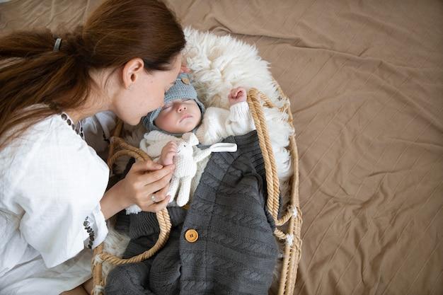 Schläfriges baby in einer weidenwiege in der wärme nahe einer glücklichen fürsorglichen mutter-draufsicht.