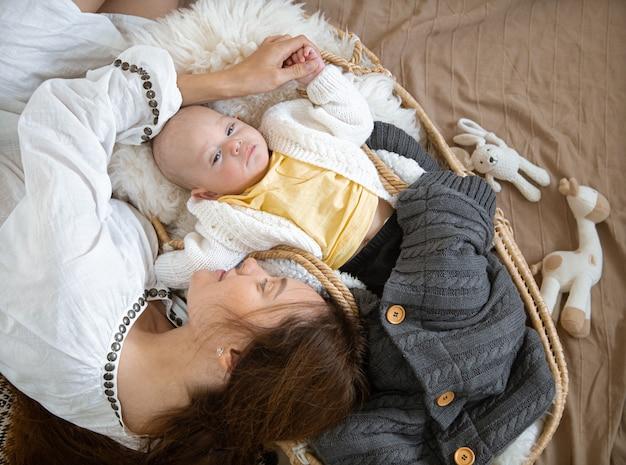 Schläfriges baby in einer weidenwiege in der wärme nahe einer glücklichen fürsorglichen mutter mit einer decke mit spielzeug draufsicht.