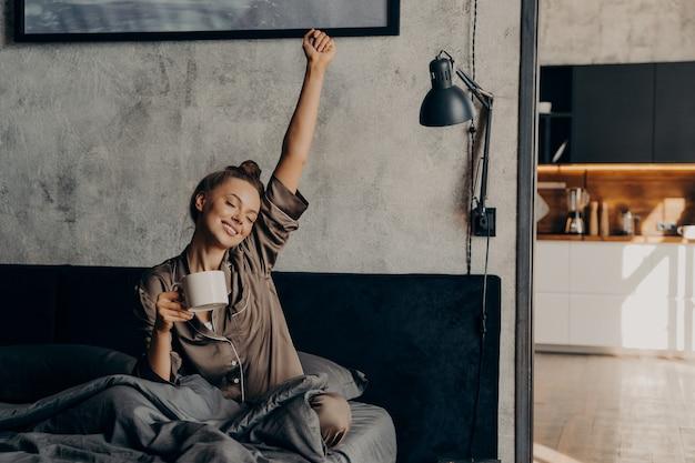 Schläfriges entspanntes schönes mädchen im satinpyjama, das versucht, mit kaffee aus dem nachtschlaf aufzuwachen