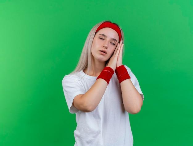 Schläfriges junges kaukasisches sportliches mädchen mit zahnspangen, die stirnband tragen