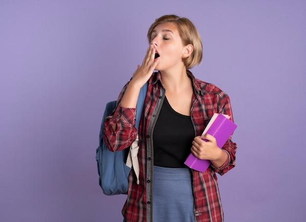 Schläfriges junges slawisches studentenmädchen, das rucksack trägt, legt hand auf mund hält buch und notizbuch