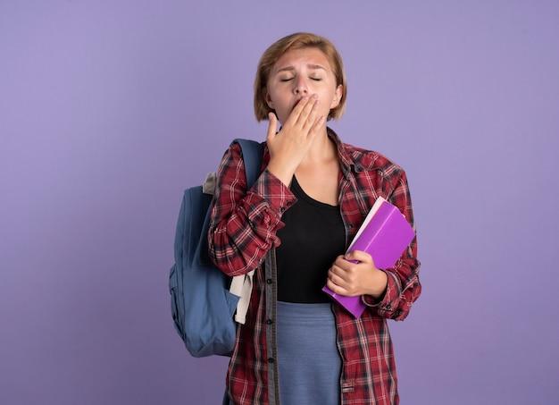 Schläfriges junges slawisches studentenmädchen mit rucksack, das hand auf den mund legt und buch und notizbuch hält holding