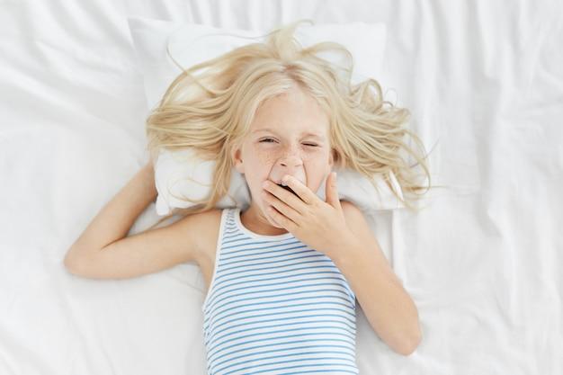 Schläfriges mädchen, das früh morgens aufwacht und den mund mit der hand bedeckt, während es gähnt, zur schule oder zum kindergarten geht. blondes charmantes kind im matrosen-t-shirt, das auf weißen bettwäsche liegt und gerade erwacht