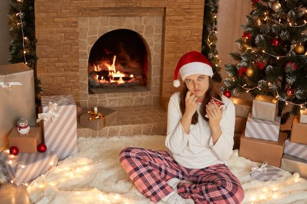 Schläfriges mädchen, das tasse heißes getränk hält, während auf boden mit gekreuzten beinen sitzt, lässige kleidung und weihnachtsmannhut nahe kamin und weihnachtsbaum trägt