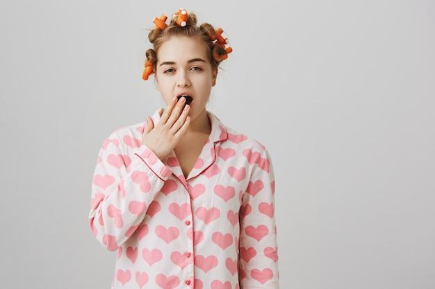 Schläfriges mädchen in lockenwicklern und pyjamas, das morgens aufwacht und gähnt