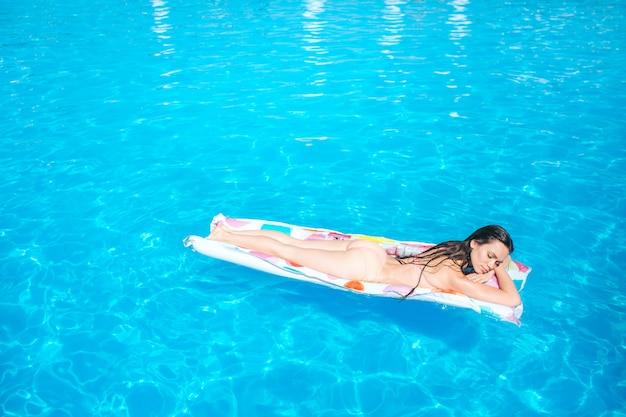 Schläfriges mädchen liegt auf der matratze und kühlt. sie bekommt etwas sonnenbräune. junge frau ist mitten im schwimmbad.