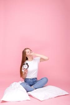 Schläfriges mädchen versucht, mit wecker auf rosa hintergrund aufzuwachen