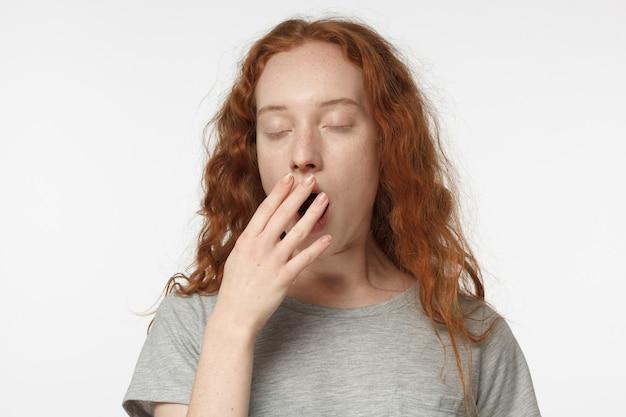 Schläfriges rothaariges mädchen gähnt und schließt den mund mit der hand