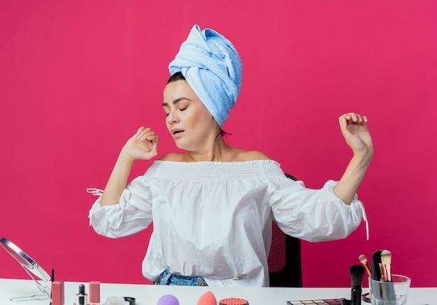 Schläfriges schönes mädchen sitzt am tisch mit make-up-werkzeugen gähnt isoliert auf rosa wand