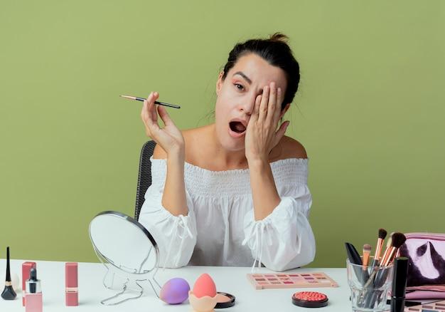 Schläfriges schönes mädchen sitzt am tisch mit make-up-werkzeugen setzt han auf gesicht suchen hält make-up-pinsel isoliert auf grüner wand