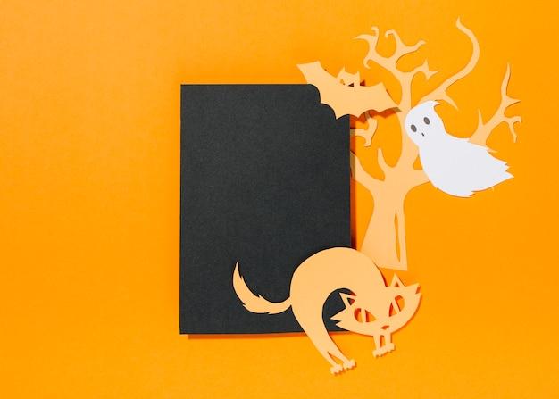 Schläger und katze auf blatt papier mit baum hinten und geist, die nahe fliegen