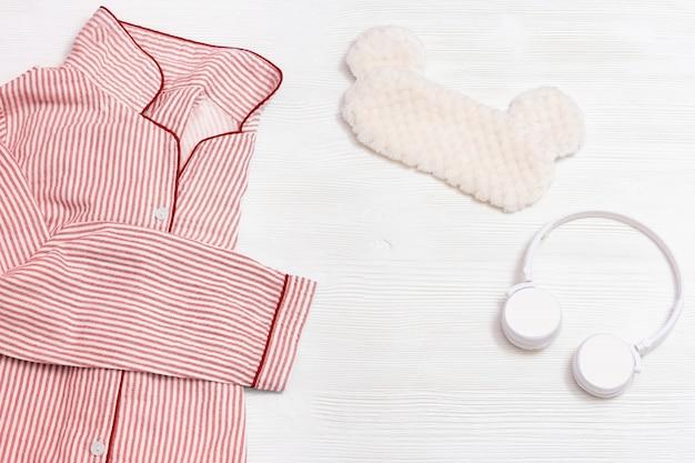 Schlafanzug pyjama, kopfhörer, lustige augenmaske zum schlafen mit tierohren auf weißem holz mit kopierraum.
