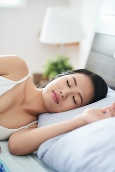 Schlafende asiatische frau auf dem bett