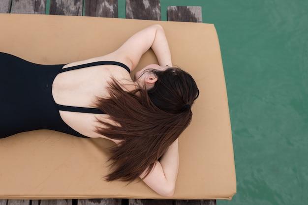 Schlafende frau am strand, junge asiatische frau sonnenbaden am strand, asiatische frau lebensstil.