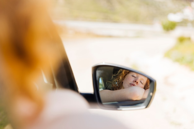 Schlafende frau im autoseitenspiegel