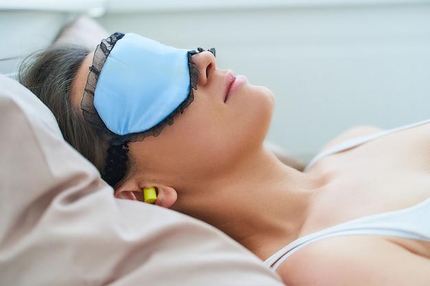 Schlafende frau mit augenmaske und ohrstöpseln für besseren schlaf, lärmschutz und süße träume