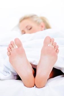 Schlafende frau mit sauberen füßen, die unter der bettdecke hervorstehen