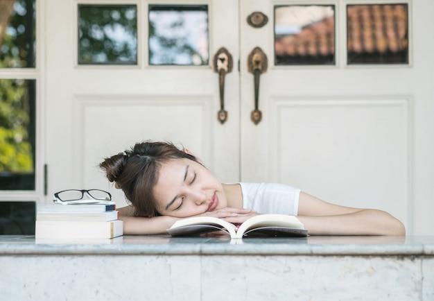Schlafende frau, nachdem sie für das lesen auf marmortabelle vor haus müde war