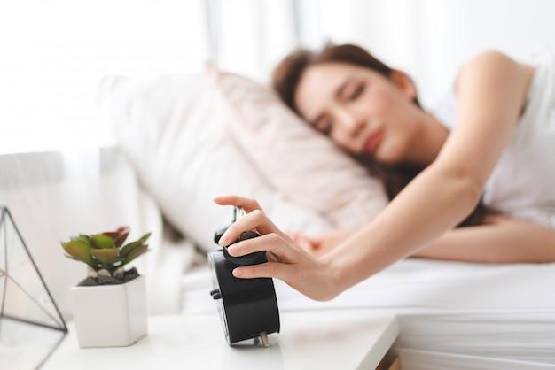 Schlafende frau und wecker im schlafzimmer zu hause