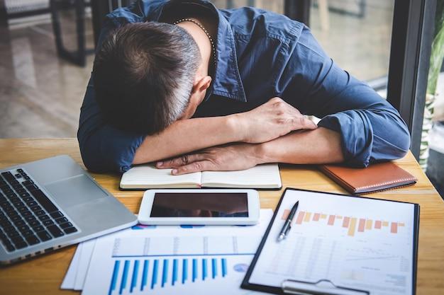 Schlafender geschäftsmann, müder älterer geschäftsmann, der langen arbeitstag habend überarbeitet auf tabelle in seinem büro schläft