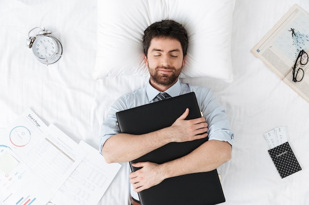 Schlafender hübscher junger geschäftsmann am morgen im bett liegt und hält falltasche