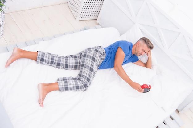 Schlafender kerl zu hause. schlafstörungen. guter und gesunder schlaf. gut aussehender mann im bett. depression beim aufwachen, beschrieben von den betroffenen als tiefe traurigkeit, mangel an lust am tag. mangel an motivation.