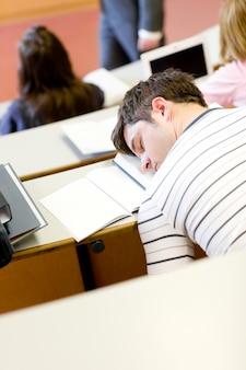 Schlafender männlicher student während einer universitätslektion