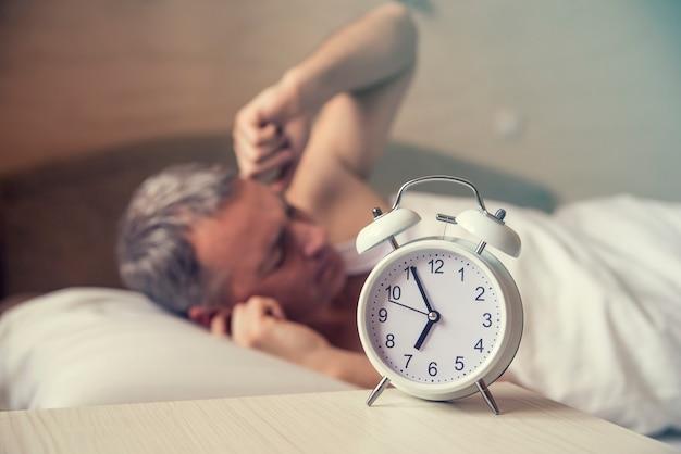 Schlafender mann gestört durch wecker am frühen morgen. verärgerter mann im bett durch lärm geweckt wakeed up der mann liegt im bett und schaltet am morgen um 7 uhr einen wecker aus