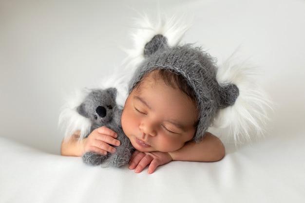 Schlafender säugling, der friedlich kleines neugeborenes mit niedlichem grauem hut und spielzeugbär legt