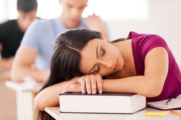 Schlafender schüler. schöne studentin, die im klassenzimmer schläft