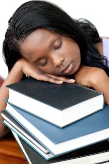 Schlafender student, der auf einem stapel büchern sich lehnt
