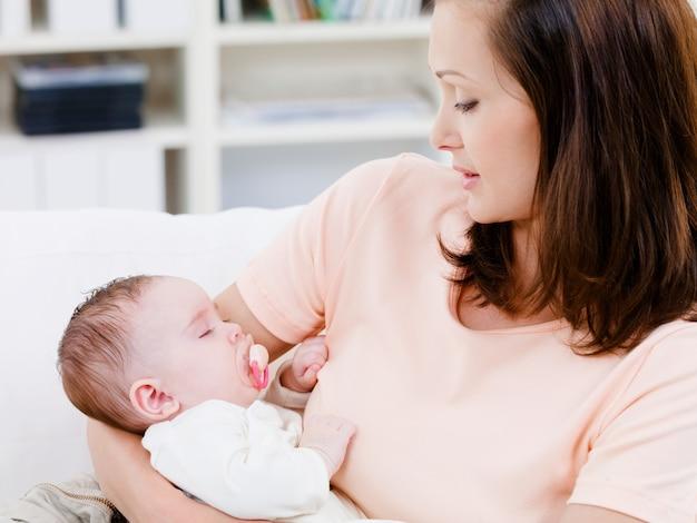 Schlafendes baby an den händen der mutter